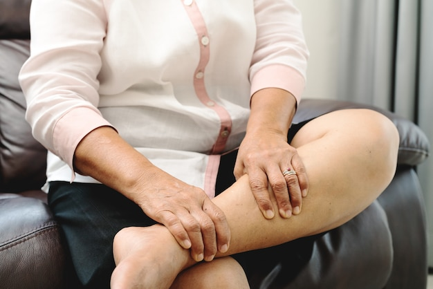 Senior woman suffering from leg cramp pain at home