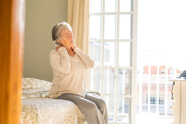Senior woman suffering from neckache after sleep, rubbing stiff muscles, old female sitting on bed touching neck feeling discomfort because of uncomfortable bed at home