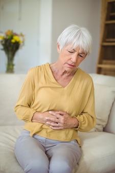 リビングルームで胃の痛みに苦しんでいる年配の女性