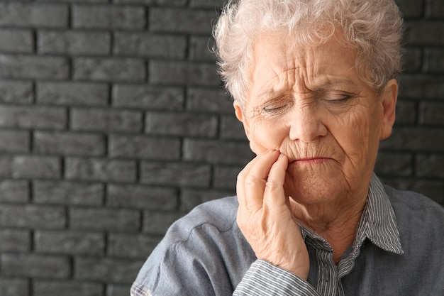 Senior woman suffering from toothache on dark background