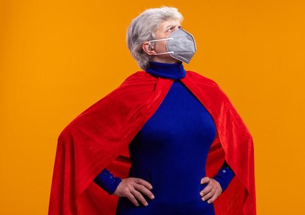 赤いマントと顔の保護マスクを身に着けている年配の女性のスーパーヒーローは脇を見て
