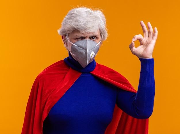 赤いマントと顔の保護マスクを身に着けている年配の女性のスーパーヒーローは、オレンジ色の背景の上に幸せで前向きに立ってokサインをしているカメラを見て