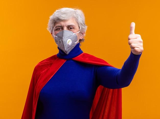 赤い岬と顔の保護マスクを身に着けている年配の女性のスーパーヒーローは、オレンジ色の背景の上に立って親指を示して幸せでポジティブなカメラを見て