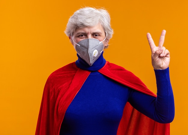 赤いマントと顔の保護マスクを身に着けている年配の女性のスーパーヒーローは、オレンジ色の背景の上に立っているvサインを示す幸せでポジティブなカメラを見て