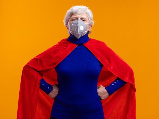 赤いマントと顔の保護マスクを身に着けている年配の女性のスーパーヒーローは、オレンジ色の背景の上に立っている腰に腕で自信を持って表情でカメラを見て