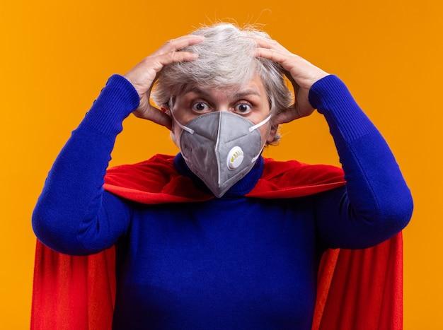 カメラを見ている赤いマントと顔の保護マスクを身に着けている年配の女性のスーパーヒーロー