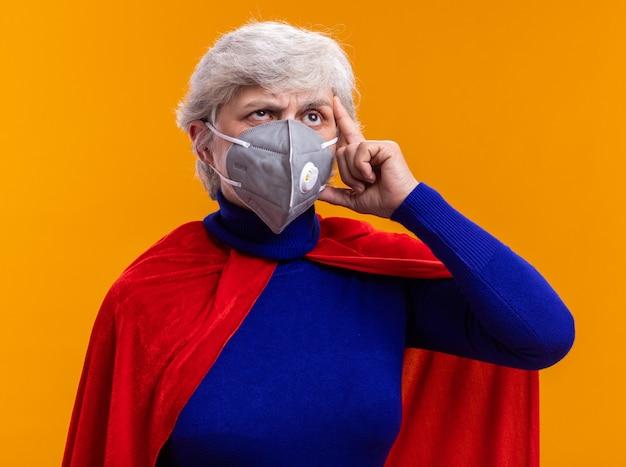 オレンジ色の上に立って困惑して見上げる赤いマントと顔の保護マスクを身に着けている年配の女性のスーパーヒーロー