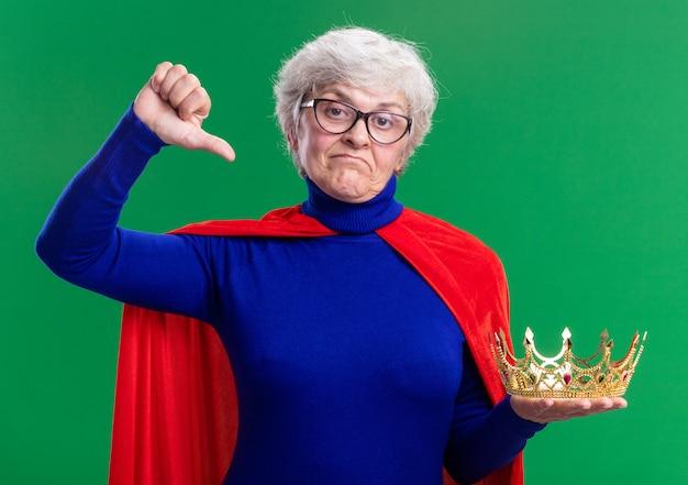 赤いマントと眼鏡をかけた年配の女性のスーパーヒーローが不機嫌そうに見える王冠を保持