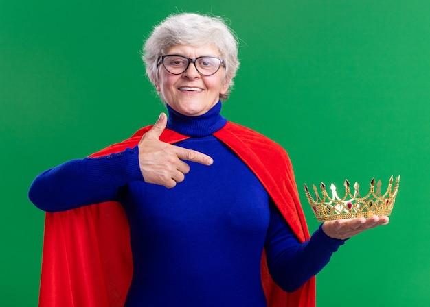 赤いマントとメガネを身に着けている年配の女性のスーパーヒーローは、緑の背景の上に立って自信を持って笑って人差し指で指している王冠を保持しています