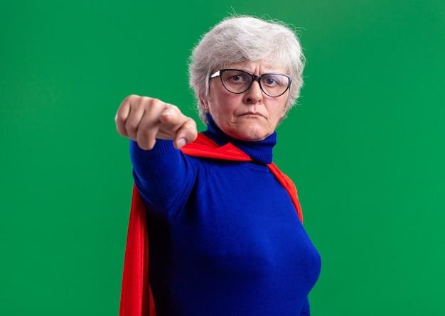 カメラに人差し指で指す赤いマントと眼鏡を身に着けている年配の女性のスーパーヒーロー