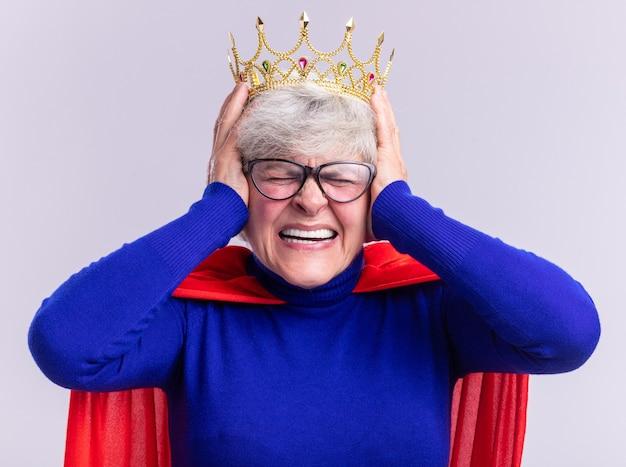 白い背景の上に立っているイライラした表情で手で耳を閉じるカメラを見て頭に王冠と赤いマントとメガネを身に着けている年配の女性のスーパーヒーロー