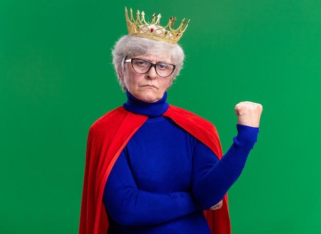 カメラを見て頭に王冠と赤いマントと眼鏡を身に着けている年配の女性のスーパーヒーロー