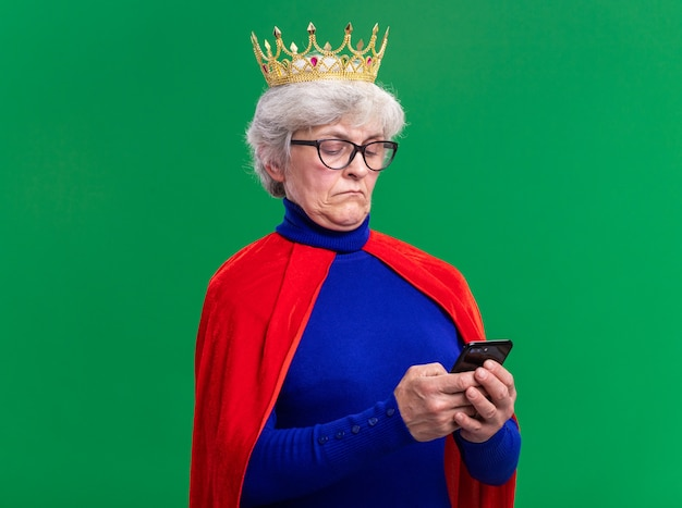 緑の背景の上に立って自信を持って見えるスマートフォンを使用して頭に王冠と赤いマントと眼鏡を身に着けている年配の女性のスーパーヒーロー