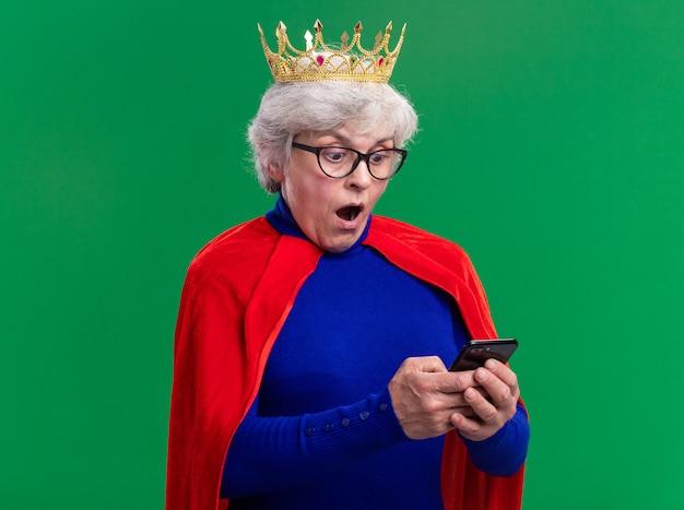 緑の背景の上に立って驚いて見えるスマートフォンを使用して頭に王冠と赤いマントと眼鏡を身に着けている年配の女性のスーパーヒーロー