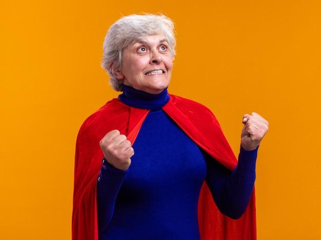 Supereroe donna anziana che indossa un mantello rosso che stringe i pugni felici ed eccitati in piedi su sfondo arancione
