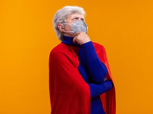 Supereroe donna anziana che indossa mantello rosso e maschera protettiva facciale che guarda da parte Foto Gratuite