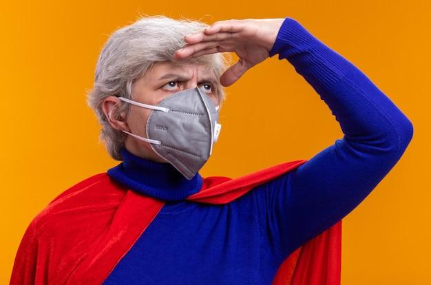 Supereroe donna anziana che indossa mantello rosso e maschera protettiva facciale che guarda lontano con la mano sopra la testa in piedi su sfondo arancione