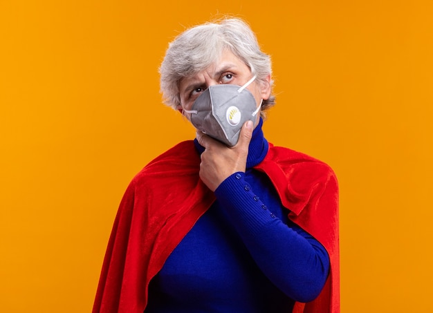 Supereroe donna anziana che indossa mantello rosso e maschera protettiva facciale che guarda perplesso in piedi sopra l'arancia
