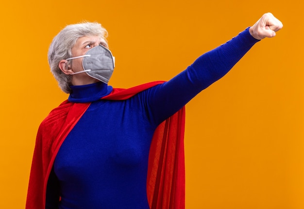 Supereroe donna anziana che indossa un mantello rosso e una maschera protettiva facciale che fa il gesto del vincitore