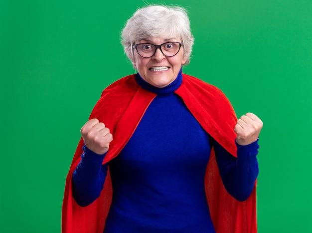 Senior donna supereroe che indossa mantello rosso e occhiali stringendo i pugni felici
