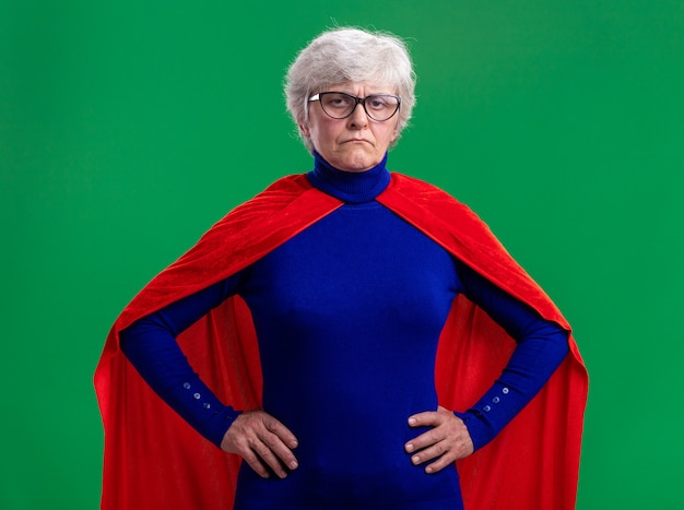 Senior woman superhero wearing red cape and glasses looking at camera with serious face with arms at hip standing over green background