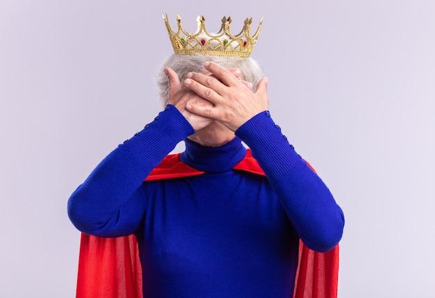 Supereroe donna anziana che indossa mantello rosso e occhiali con corona sulla testa che copre gli occhi con le mani in piedi su sfondo bianco