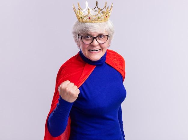 Supereroe donna anziana che indossa mantello rosso e occhiali con corona sulla testa guardando la telecamera Foto Gratuite