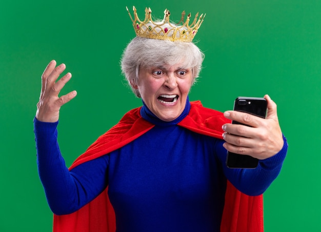 Supereroe donna anziana che indossa mantello rosso e occhiali con corona sulla testa guardando lo schermo del suo smartphone urlando con espressione aggressiva in piedi su sfondo verde