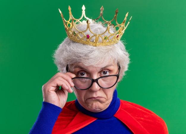 Supereroe donna anziana che indossa mantello rosso e occhiali con corona sulla testa