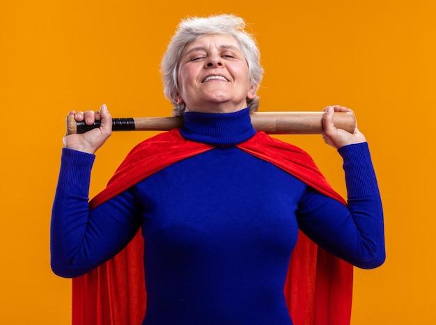 빨간 망토를 입은 여성 슈퍼히어로가 야구 방망이를 들고 주황색 배경 위에 서 있는 카메라를 보고 기뻐하고 자신감을 갖고 있다