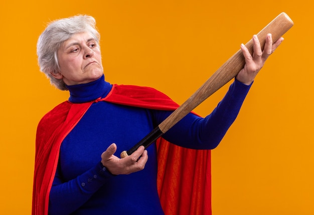 Senior donna supereroe indossando mantello rosso tenendo la mazza da baseball guardandolo incuriosito in piedi su sfondo arancione