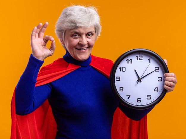 オレンジ色の背景の上に立ってokサインをやって幸せで大胆なカメラを見て時計を保持している赤いマントを身に着けている年配の女性のスーパーヒーロー