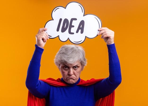Supereroe donna anziana che indossa un mantello rosso che tiene il segno del fumetto con l'idea della parola sopra la sua testa