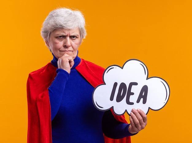 Supereroe della donna anziana che indossa mantello rosso che tiene il segno del fumetto con l'idea della parola che guarda l'obbiettivo con espressione pensierosa sul viso pensando in piedi su sfondo arancione