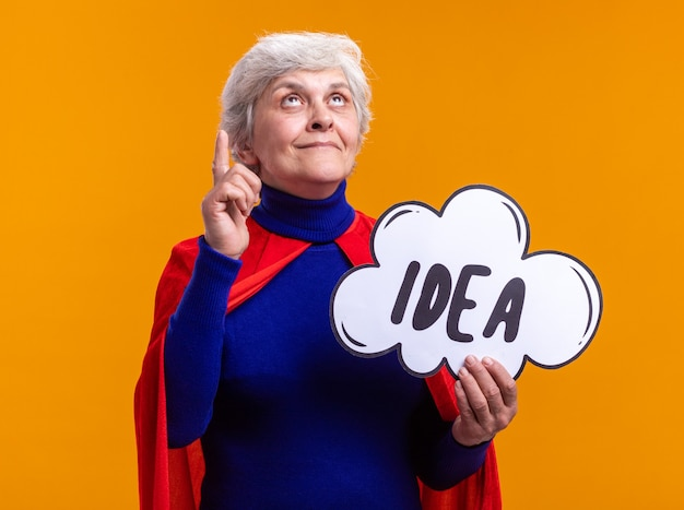 Supereroe donna anziana che indossa un mantello rosso che tiene il segno del fumetto con l'idea della parola guardando in alto con la faccia felice in piedi su sfondo arancione