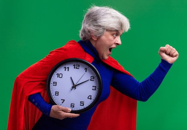도움을 서두르고 벽 시계를 들고 빨간 케이프를 입고 고위 여자 슈퍼 히어로