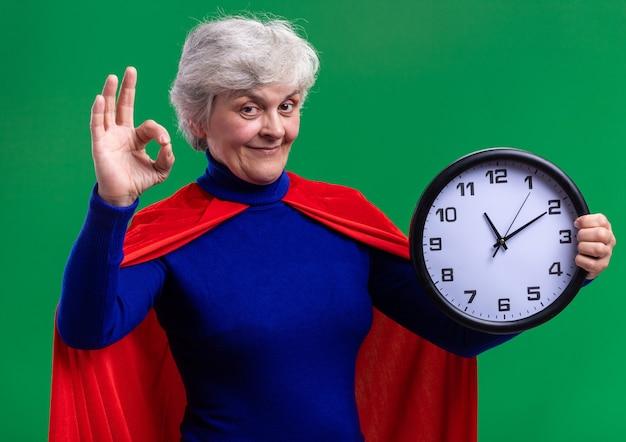 緑の背景の上に立っているokサインを示す幸せでポジティブなカメラを見て壁時計を保持している赤いマントを身に着けている年配の女性のスーパーヒーロー