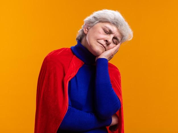 Supereroe donna anziana che indossa un mantello rosso che si appoggia la testa sul gesto del sonno della palma con gli occhi chiusi