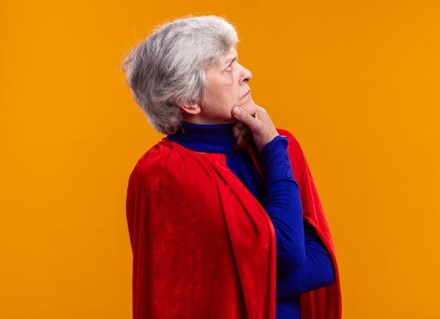 オレンジ色の上に立っている深刻な顔で脇を見て赤いマントを着ている年配の女性のスーパーヒーロー