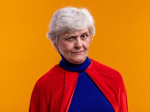 オレンジ色の背景の上に立っている懐疑的な表情でカメラを見て赤いマントを身に着けている年配の女性のスーパーヒーロー