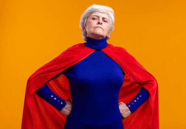 Supereroe donna anziana che indossa mantello rosso guardando la telecamera con espressione sicura con le braccia all'anca in piedi su arancione