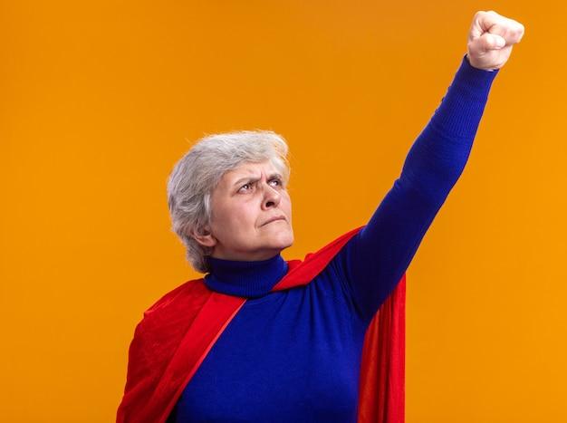 Supereroe donna anziana che indossa un mantello rosso che guarda in alto facendo il gesto del vincitore con la mano pronta ad aiutare e combattere in piedi sopra l'arancia