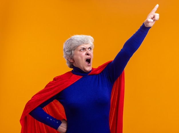 Supereroe donna anziana che indossa un mantello rosso che guarda in alto puntando con il dito indice a qualcosa che grida con un'espressione aggressiva in piedi su sfondo arancione