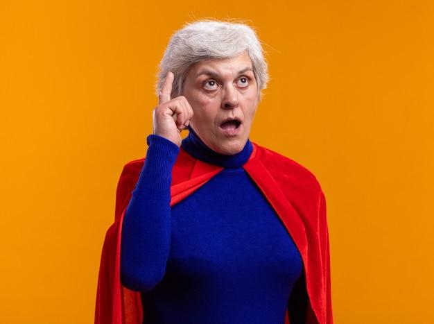 オレンジ色の上に立っている新しいアイデアを持って驚いている人差し指を見せて見上げる赤いマントを身に着けている年配の女性のスーパーヒーロー