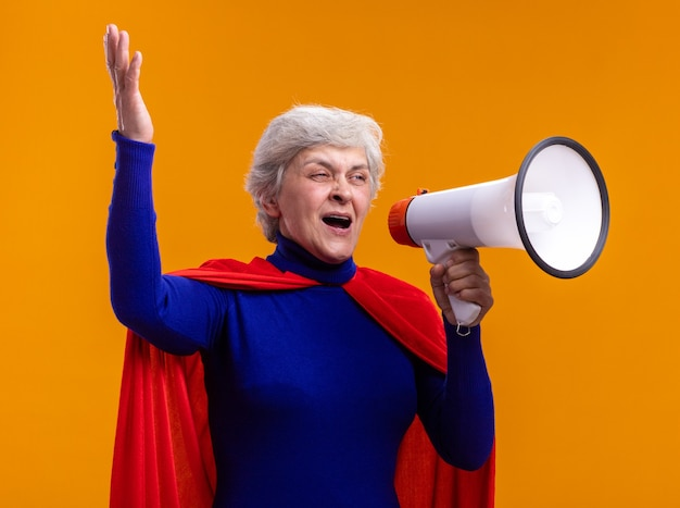 빨간 망토를 입은 고위 여성 슈퍼히어로는 주황색 배경 위에 서서 메가폰에 행복하고 흥분된 소리를 지르고 있습니다.