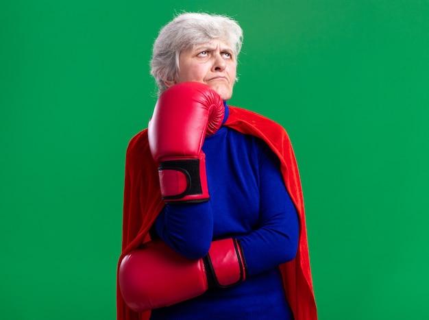 Supereroe donna anziana che indossa un mantello rosso con guanti da boxe che guarda da parte