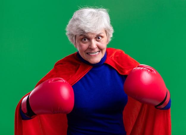 Senior donna supereroe indossando mantello rosso con guantoni da boxe guardando la telecamera tesa ed eccitata in piedi su green