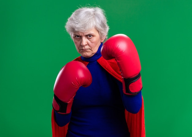 Senior woman superhero wearing red cape with boxing gloves looking at camera with serious confident expression ready to fight standing over green background