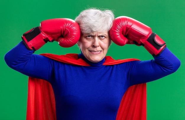 ボクシンググローブと赤いマントを身に着けている年配の女性のスーパーヒーローは、緑の背景の上に立ってイライラしてイライラして目を転がします