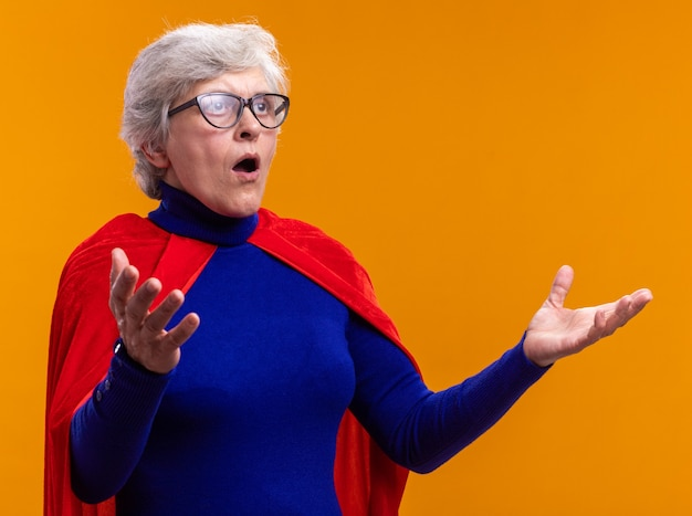 Supereroe donna anziana con gli occhiali che indossa un mantello rosso che guarda da parte stupito e sorpreso con le braccia alzate in piedi su sfondo arancione